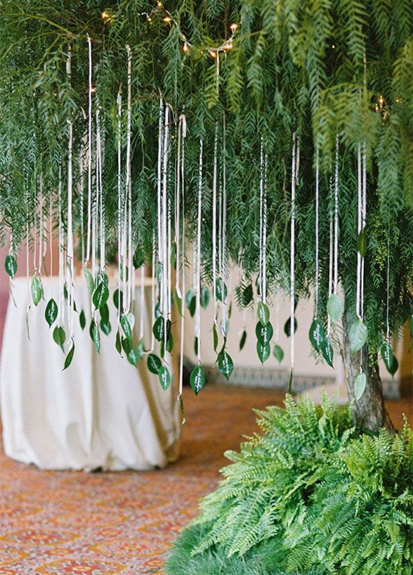 Help guests find their seat with vibrant green leaves acting as escort cards. Simple and chic idea you can DIY for your wedding.