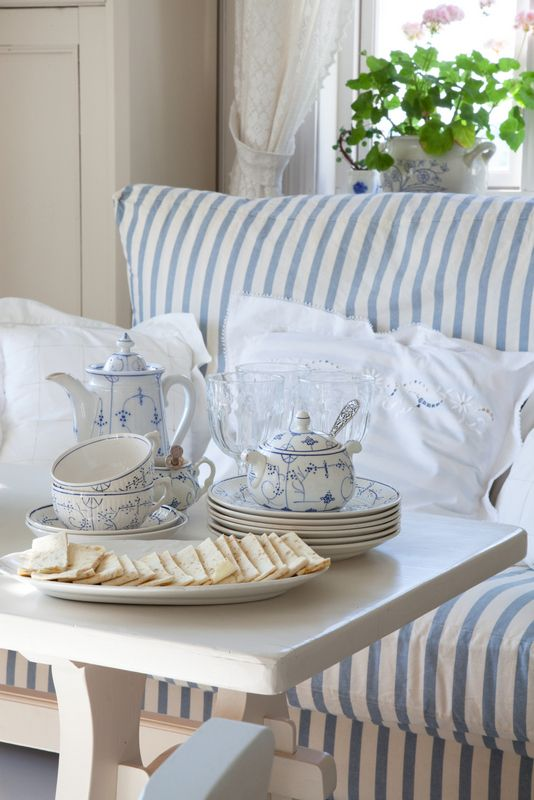 Tea time in blue and white. Love the stripes of the sofa!