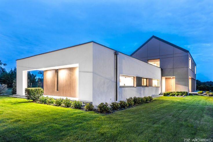 Zdjęcie nocne domu Pół-parterowego.  Duża parterowa część budynku połączona z bryłą o dachu dwuspadowych od niedawna określaną jako nowoczesna stodoła. Duży taras, elewacja z płyt oraz tynku