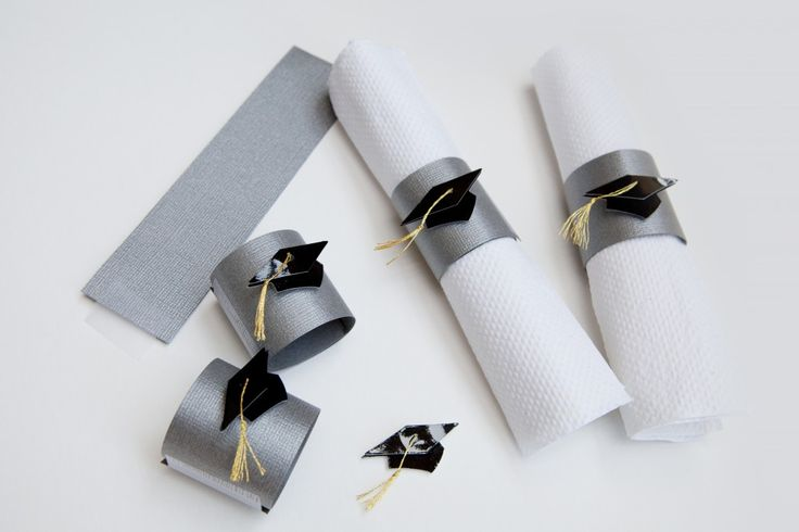or the napkin rings, you'll need to cut up a piece of cardstock into 3 inch long strips. Wrap it around the napkin and secure with tape or hot glue. Then, add a cute embellishment like these grad caps and put 'em on display.