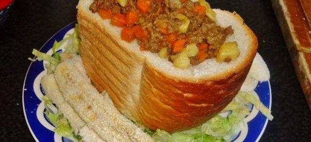 Bunny+chow+is+een+Zuid-Afrikaans+fastfoodgerecht.+Het+bestaat+uit+een+uitgehold+stuk+brood+dat+opgevuld+wordt+met+kerrie.+Het+komt+oorspronkelijk+uit+de+Indische+gemeenschap+rond+Durban. Het+gerecht+bestaat+in+meerdere+varianten,+afhankelijk+van+de+curry+waarmee+gewerkt+wordt+(schaap,+kip,+bonen).+Hier+met+een+Engelse+kruidenmix.
