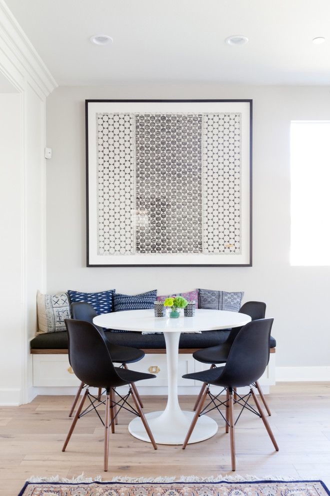 Tasteful, contemporary dining area with white, round dining table, black Eames molded plastic chairs, oversized graphic art and a built-in bench with decorative pillows | Natalie Myers