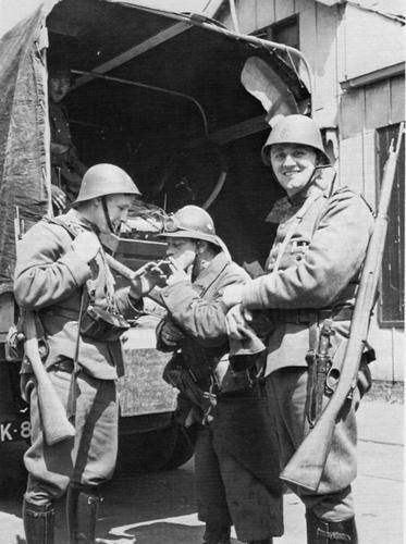 A soldier from Détachement Durand, the advance guard from the French 68ème Division d'Infanterie, shares a smoke with soldiers of Commando Zeeland, the Dutch force stationed in the province of Zeeland. Most probable date, May 10, 1940.