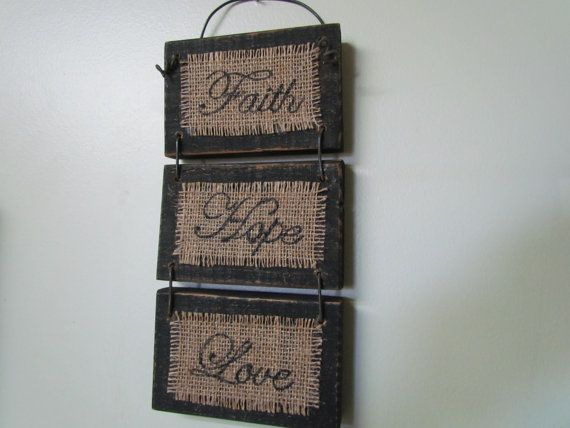 "3 Small Distressed, Black, Wooden Signs Connected With Wire Wall-hanging That Says ""Faith, Hope, Love"" Written on Burlap in a Cursive Font on Etsy, $22.00"