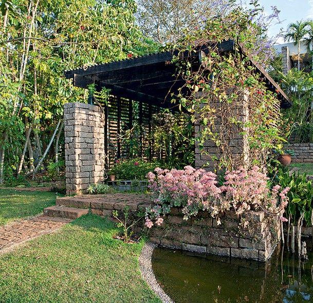 Com a função de acomodar o orquidário e o viveiro de plantas, o pergolado de ipê rústico é sustentado por duas vigas de pedra.