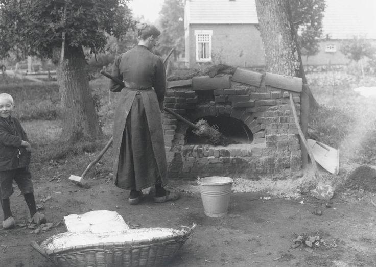 Bakoven bij het huis van Klaas Klaassens te Borger (Dr.). De oven wordt met de bezem schoon geveegd. Op de voorgrond liggen de broden in de wan die direct in de oven zullen worden geschoven. 1922 #Drente