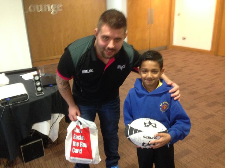 Prize winner Sahir being presented with a signed Ospreys rugby ball