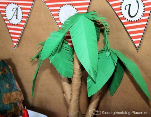 Use pool noodles covered in brown paper and green card as palm leaves