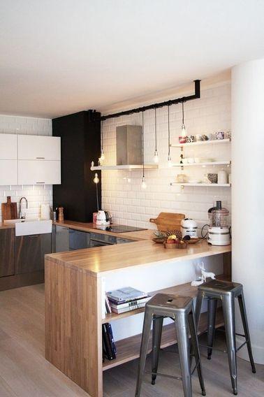 Une cuisine avec bar est généralement ouverte sur le salon ou sur la salle à manger : la déco cuisine devient ainsi partie intégrante du look de la maison. Le choix du bois et du carrelage métro apporte du caractère à cette cuisine grise et blanche. L'éclairage est assuré par de simples ampoules au bout de leur fil électrique enroulé autour d'une tringle pour un style industriel. On retient cette astuce d'éclairage, à décliner sur une poutre en bois ou une canalisation au plafond.