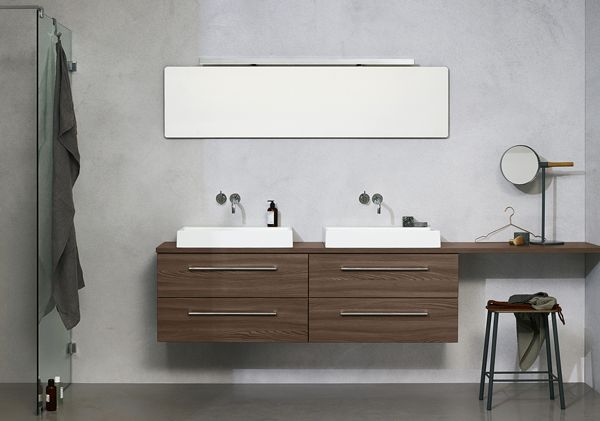 Go with the minimalistic and strictly symmetrical double washbasin – then break it up by extending the counter top and adding a vanity space on one side only.