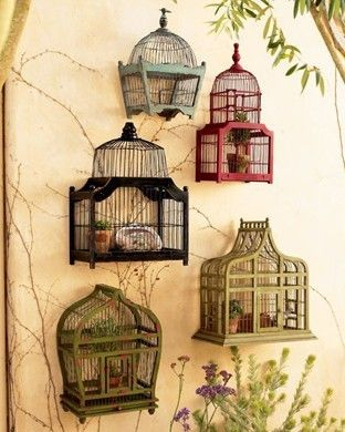 Collage of decorative bird cages on outside wall adds visual interest.  An appealing idea if also using plants in the garden which attract birds.