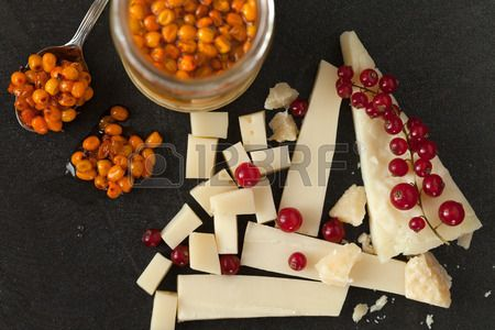 Platter with different types of cheese, redcurrant and sea buckthorn jam. Stock Photo