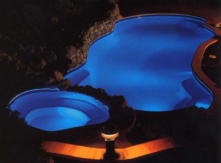 Swimming Pool. Dark Blue Pool Lights From The Water Decorate With Brown Lamp In Deck