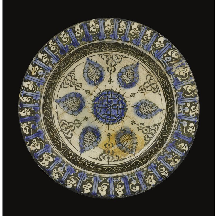 A Kashan underglaze decorated footed dish, Persia, circa 1200 of shallow form with flattened rim and high spreading foot, painted in shades of cobalt blue and black under a transparent glaze, the interior with a central knot-form medallion surrounded by six radial leaf-shaped motifs separated by black arabesques, the cavetto with a band of naskh reserved in black, the rim with a blue pseudo-kufic band on a leaf scroll ground, the back with a scalloped border above sprays of waterweed in…