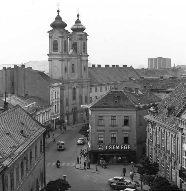 Városház tér, jobbra a Püspöki palota. Szemben a Fő (Március 15.) utcában a Nepomuki Szent János-templom és rendház