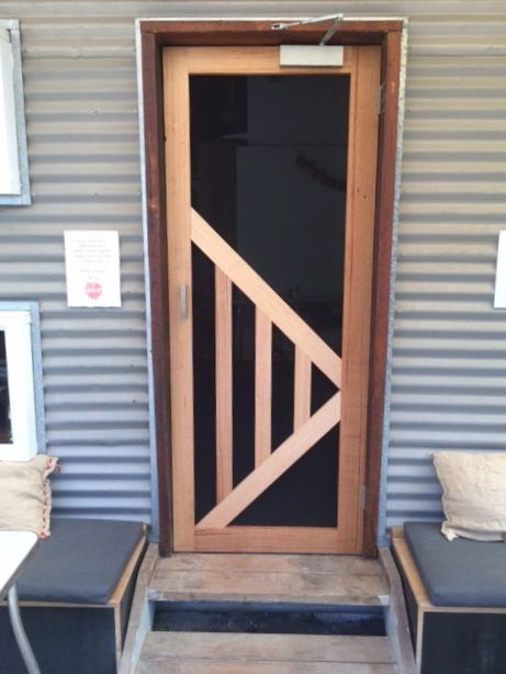 RedBeard Bakery 2015, designing & making a fly screen door for a high-traffic doorway that can handle being bumped open by cafe staff with their hands full. The angle bracing strengthens the frame & covers the high impact areas of the door. This door is a shift from the symmetry of wooden screen doors based on mortise & tennon perpendicular joins. Contemporary joining methods can escape this. There you go, more than you wanted to know about a design leap on a simple door in country bakery!