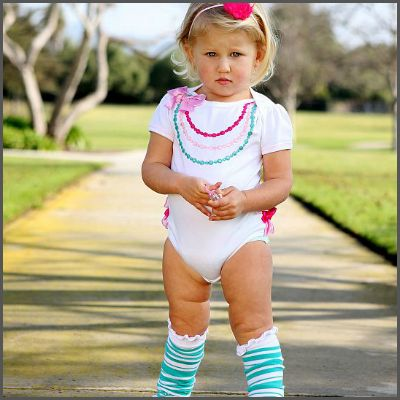 White Fancy Necklace One Piece. Your little lady will feel like a princess in this sweet, stand-out body suit. With 3 rows of applique pearls and a satin waterfall of rear ruffles, she is sure to be showered in compliments! It's also machine washable.