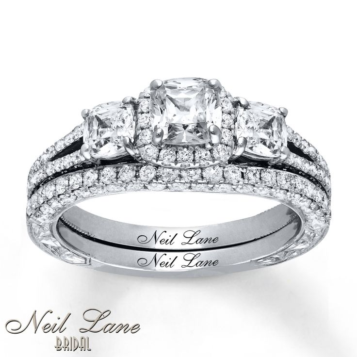 This breathtaking engagement ring from the Neil Lane Bridal® collection features three cushion-cut diamonds as its spellbinding center. Round diamonds trace two rows to form the lacy band and frame the center, while additional round diamonds line the contoured wedding band. Crafted of 14K white gold, the rings have a total diamond weight of 2 1/5 carats. Each Neil Lane Bridal® ring is hand-crafted and undergoes a four-step process which gives the ring its beautiful shin...