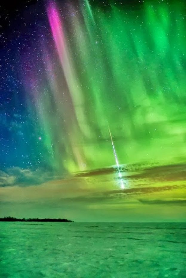 A meteor entering the earth's atmosphere with the loud boom and flash of light through Aurora Borealis in Quebec, Ontario, Canada