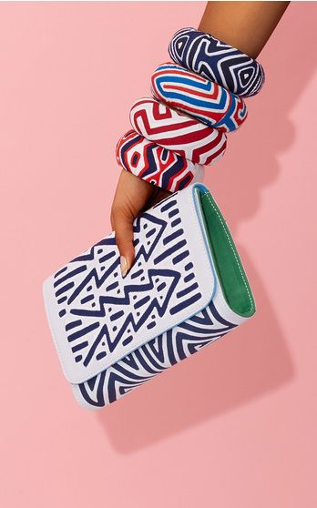 The designer: Yasmin Sabet used molas (decorative fabrics made by the indigenous community of Pamama and Colombia) to create her one-of-a-kind clutches. This season it's about: Holiday bags that easily transition from street to beach (mini sizes are new this season) and wooden mola-covered bangles. The piece to buy: Stack the fabulous bangles all the way up your arm.