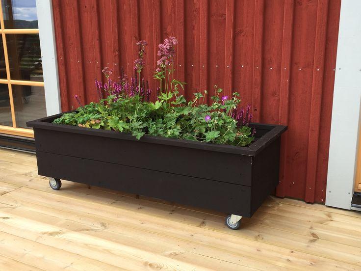 Blomlåda på hjul av återvunna fasadbrädor ommålad med Falurödfärg, svart.