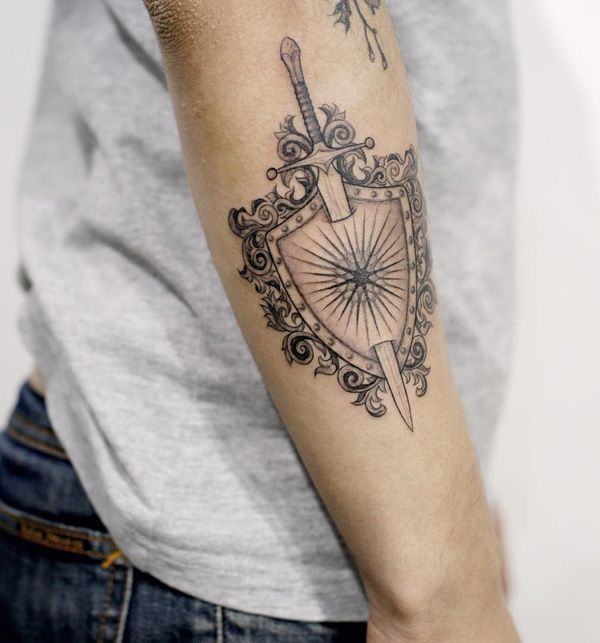 Me personally, this tattoo is probably for defender of freedom and justice. Sword and shield. Sword can be a symbol of holy war, a holy war is primarily an internal war with yourself …