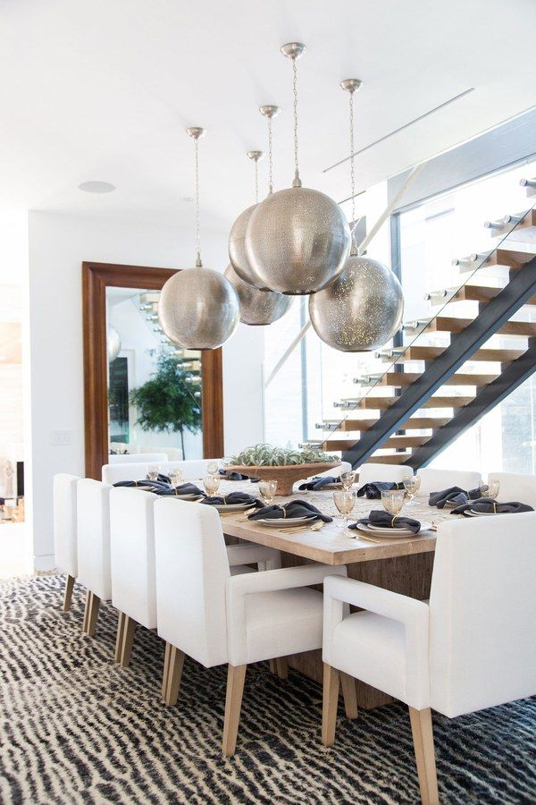 Inspired by the Spanish- and Moroccan-influenced light fixtures at Javier's in Newport Beach, a cluster of pendants from Dovetail hangs above a dining table and custom-made chairs by Blackband Design | archdigest.com