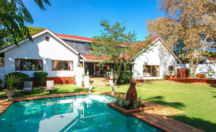 SPACIOUS FAMILY HOME WITH SEPARATE COTTAGE  The entrance hall of this welcoming family home leads via a high-ceilinged lounge with Jetmaster fireplace, onto a large entertainment area, with built-in bar and gas braai. The double doors open onto the patio, providing a cool summer environment and a homely winter evening with roaring fire. #northcliff #johannesburg #pamgolding