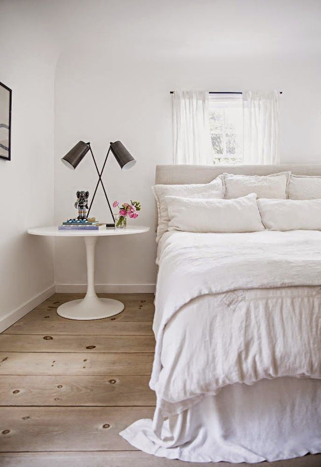 Romantic whit bedroom with linen bedding, Saarinen style bedside table, and modern lamp. #frenchcountry #europeanfarmhouse #bedroom #neutral
