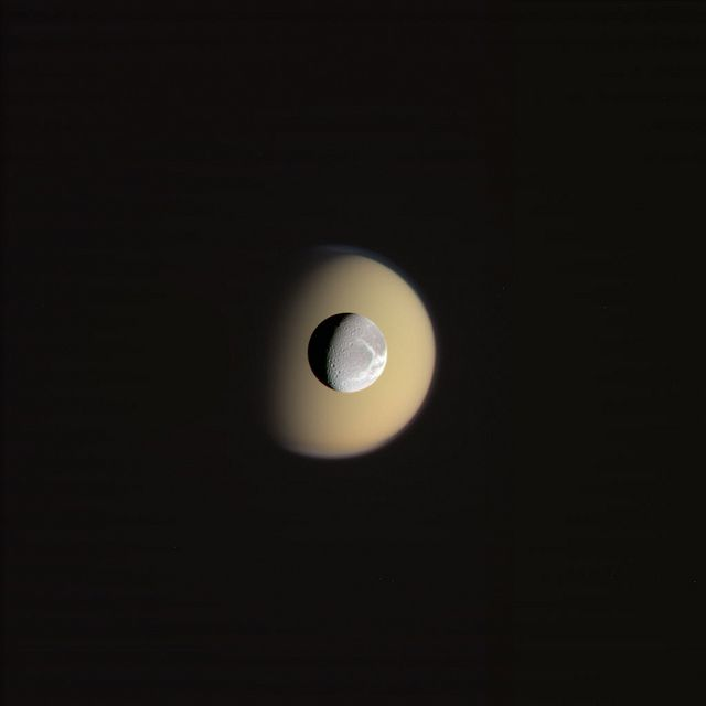 Dione in front of Titan - 2 of Saturn's many moons