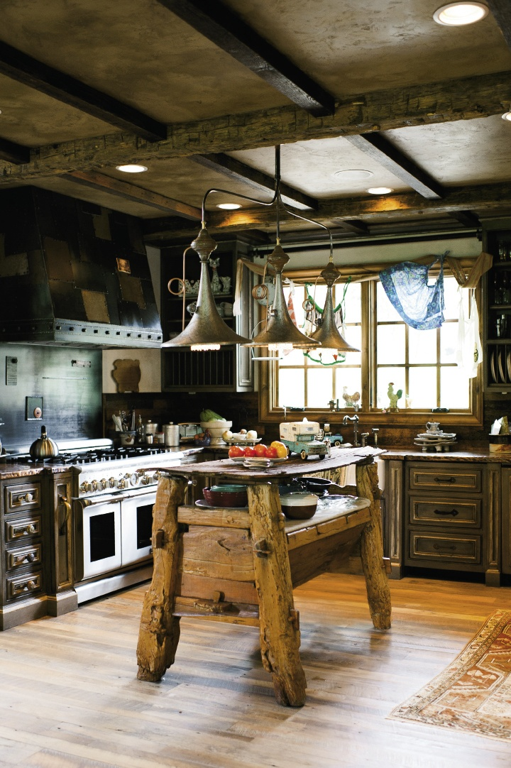 The island anchoring the kitchen, which features custom cabinetry and metal work, was assembled by affixing an old outhouse door