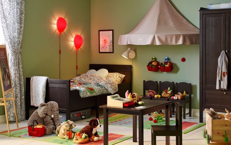 Children's bedroom with matching wood bed, chairs, wardrobe and table. Soft toys on the floor, table set up to play shop.