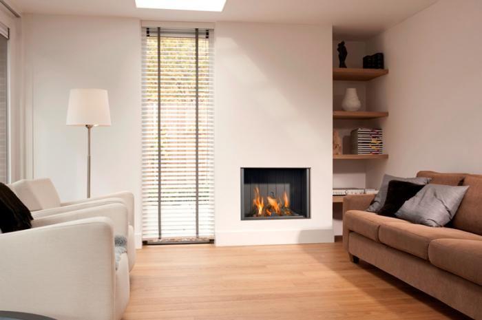 Moderne inbouw haard in hoge witte kolom, naast een nis met houten planken en raampartij   Profires partner Reijnhoudt & van der Zwet · inspiratie voor sfeerverwarming