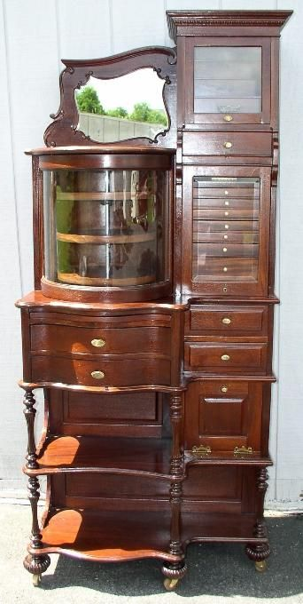 This is one of the best Ransom & Randolph Dental Cabinets ever made.     Solid Mahogany  Raised Paneled sides, Finished Back and Revolving Glass Door.    The Glass Door over the small drawers slides up into the cabinet to reveal a   Removable Traveling Dental Case.     The Glass Door on the top right slides straight up.  This cabinet is from the late 1800's.