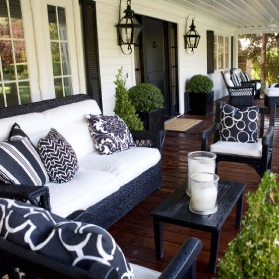 lovely front porch - love the black furniture and light fixtures. Love the floor color too.