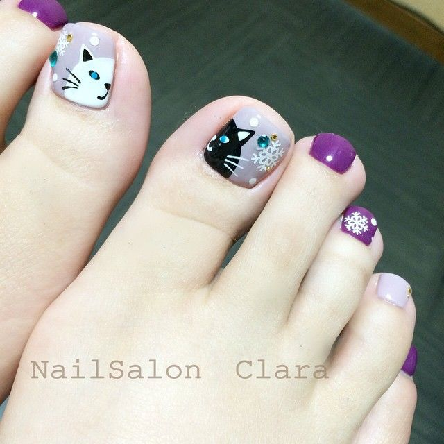 Pretty pedicure: Shades of purple with a black and white cat face on each of the big toe nails, and a couple of snowflakes. I love this