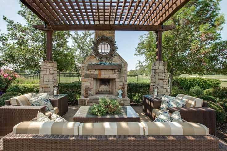 This outdoor living space at the Jonas Brothers' Texas home has an elegant pergola and stone fireplace with neutral furniture.