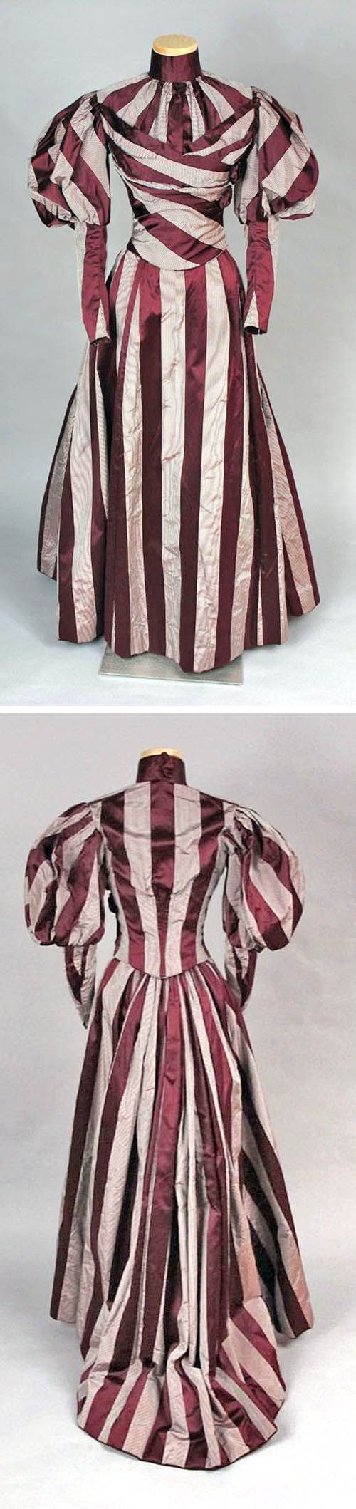 Two-piece day dress, ca. 1897. Maroon silk satin with plain-woven stripes of thin white & black stripes lined with tan cotton. Closely fitted, with boned seams & darts. Skirt has very narrow pleats every few inches for ease of movement; pocket in rear right seam. emuseum of the Connecticut Historical Society 1945.1.1115ab: