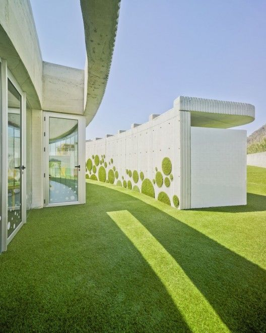 NURSERY-SCHOOL / Rocamora Arquitectura (Spain). Curving organic walls promote movement. Grass wall textures promote interaction with it.