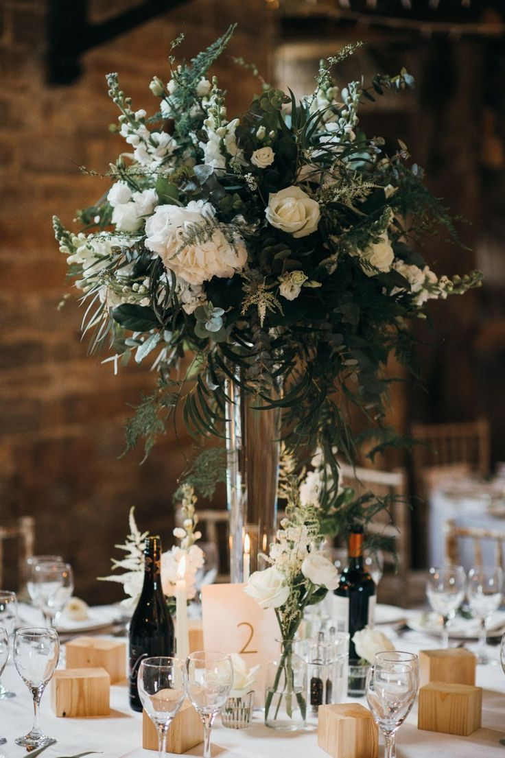 Gorgeous white and green tall floral centrepieces on round wedding reception tables.