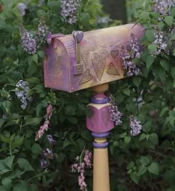 Produce a themed mailbox with nothing more than paint and stencil. This mailbox was sponge painted and goes well with the purple lilacs that surround it.