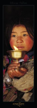 Tibetan Buddhist woman offering butter lamp