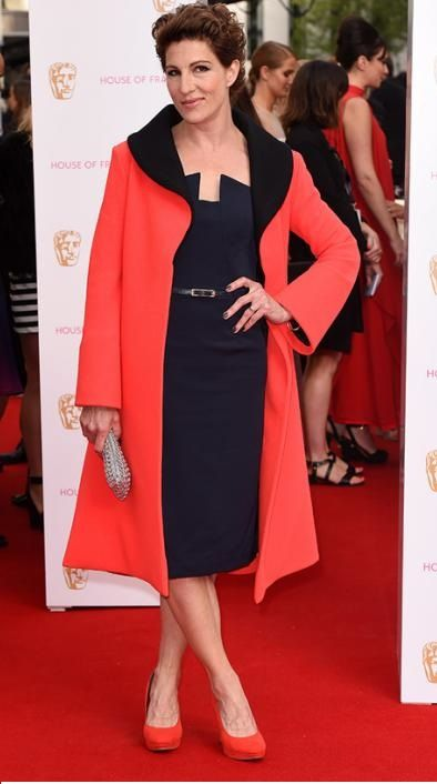 Tamsin Greig wearing Elizabeth Caitlin Ward's amazing flame colored coat and sleek slate sexy dress! Powerhouse!
