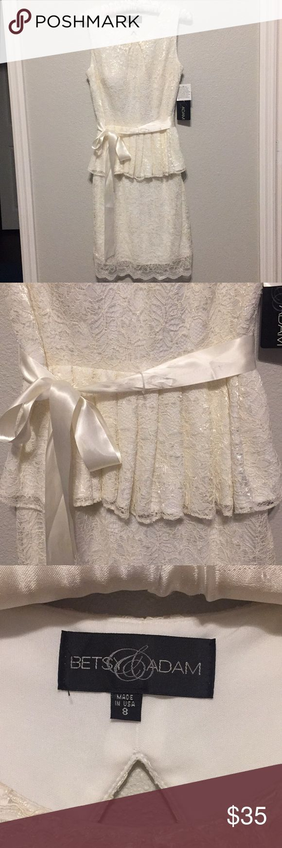 Gorgeous dress! Beautiful ivory dress. Gorgeous lace. Peplum style. Side zipper. Open back. Knee length. Satin belt is attached on the zipper's side; however, it can be arranged on the front or back. Tags still attached. Betsy & Adam Dresses Wedding