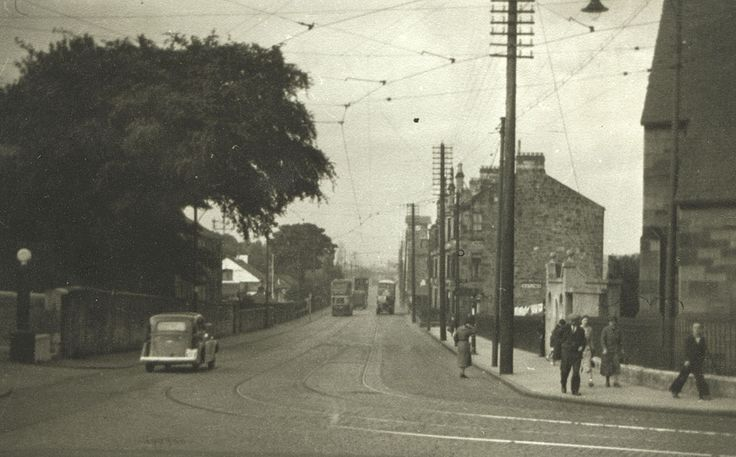 This view of Pollokshaws Road looking north from the Round Toll was taken around 1959, before the wholesale redevelopment of Pollokshaws in the 1960s. In the foreground, right, is the original Pollokshaws Methodist Church. The structure beside it on the edge of the pavement is a gents' toilet and beyond that is the Afton Terrace tenement. The clock tower of Pollok Academy is visible further down the street, on the right - TheGlasgowStory