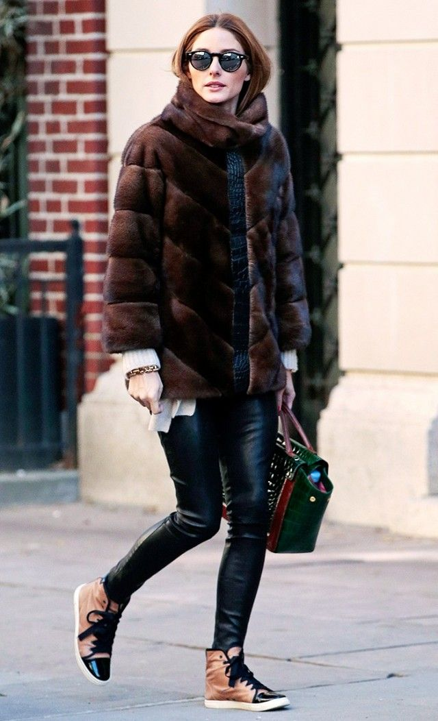 Olivia Palermo wears a fur coat, leather leggings, high-top sneakers, mirrored sunglasses, and a leather tote bag