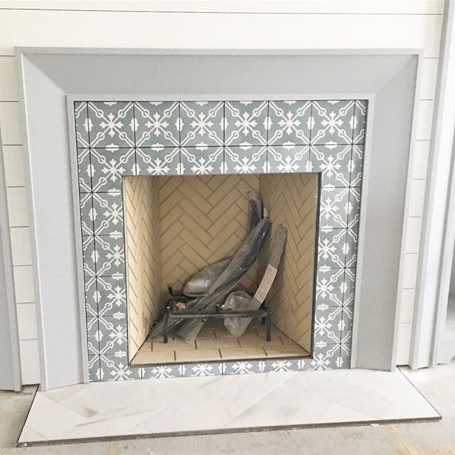 I'm having serious fireplace envy after seeing this beauty designed by @gretchenblack. How about you? From the concrete tile surround to the honed marble laid on a herringbone design for the hearth. Shiplap surrounding the mantel painted Coventry Grey by @benjaminmoore it's a winner in my book. #glenviewpark7