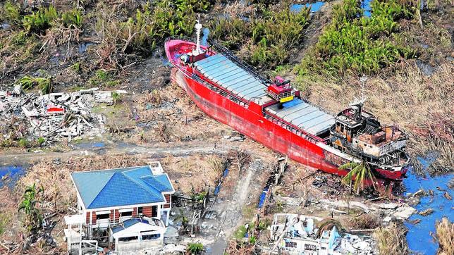 Un barco entre las casas en Tacloban (Filipinas)