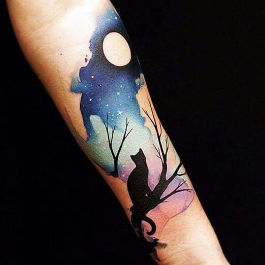 Night sky and cat tattoo on arm.