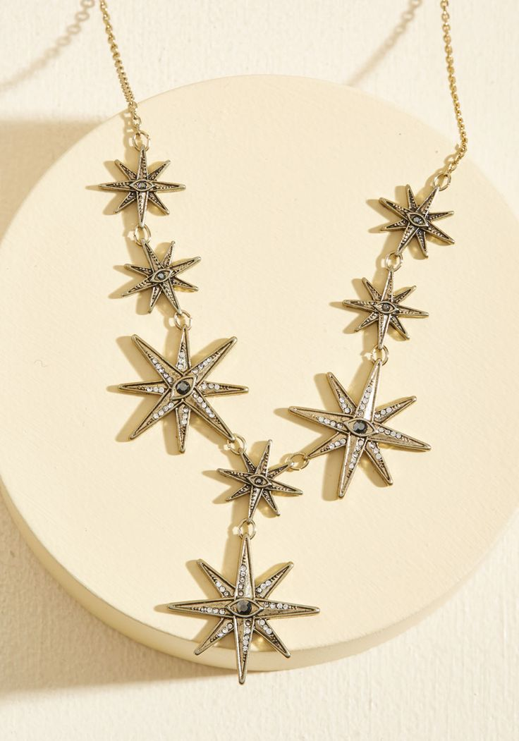 Wish Upon a Starburst Necklace | Mod Retro Vintage Necklaces | ModCloth.com  Wherever you find yourself tonight, this golden necklace is certain to fulfill your heart's desire for a stylish look. With gleaming rhinestones and eye-like accents, this starburst-shaped accessory guarantees a future of fashionable occasions while its pendants adorn your ensemble.